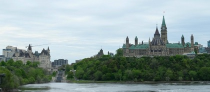 A view of the river side of the Parliament Buildings and the Chateau Laurier Hotel, with the Rideau Canal in the middle as it ends at the Ottawa River.